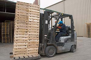 Photograph of a forklift filling a heat treatment chamber.