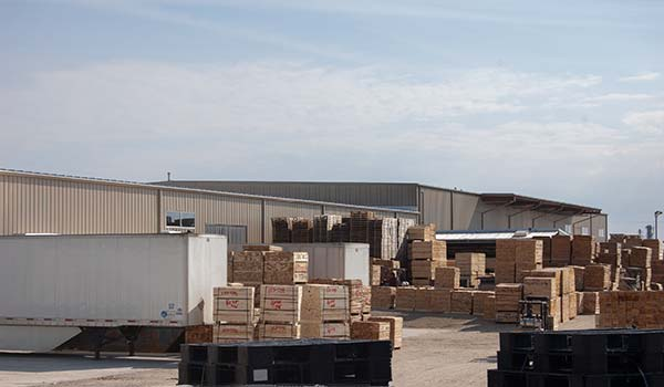 Photograph portraying the facility and its huge stacks of precision-cut lumber.